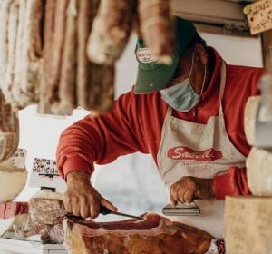 salumiere con mascherina anti covid che taglia il salame